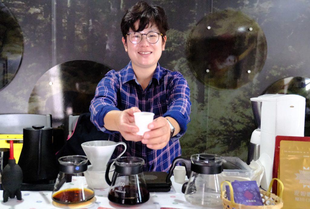 """來自富源村的""""泥妲咖啡""""的戴豐秋女士遞咖啡給來賓品嘗"""