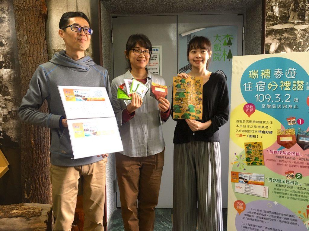 三位來自瑞穗鄉公所的工作人員在展示茶包、瑞穗泛舟券和瑞穗旅遊地圖給媒體拍攝